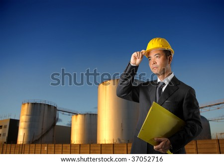 asian engineer with factory on the background - stock photo