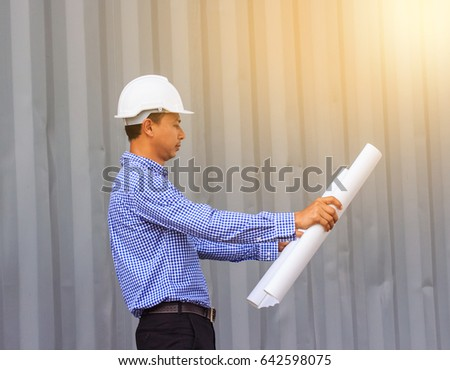 Asian Engineers looking at a plan on a construction site