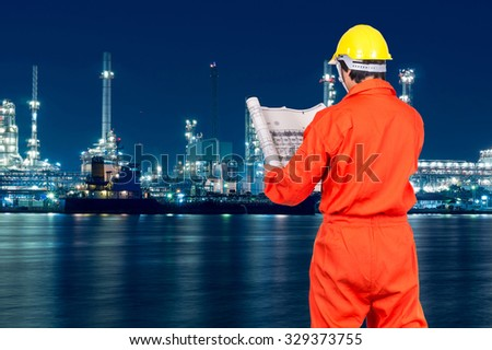 Asian engineers looking at the blueprint on Oil and gas refinery or Petrochemical factory at twilight time, industrial concept - stock photo