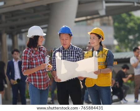 Asian engineers man and woman working in site building city background