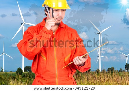 Asian engineers thinking and holding the note pad on Wind turbine power generator with world map, industrial concept, Elements of this image furnished by NASA