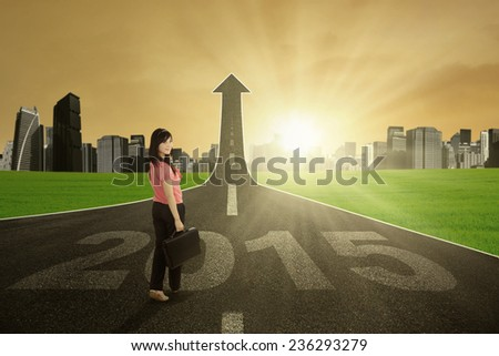 Asian entrepreneur standing on the street with number 2015 turning into arrow upward - stock photo