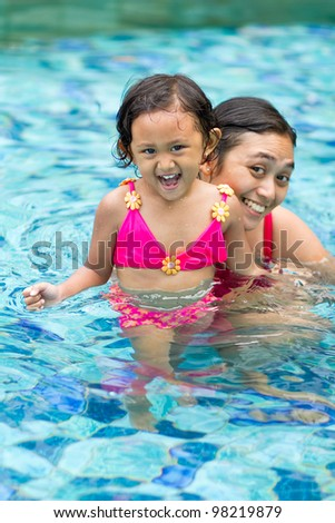 asian ethnic child and mother fun in swimming pool together - stock photo