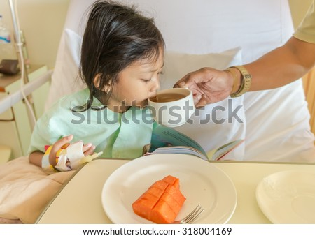 Asian Ethnic Little Girl Patient in Hospital Drinking Tea Helped by Her Father - stock photo