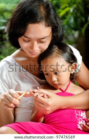 asian ethnic mom cutting little girl fingernail