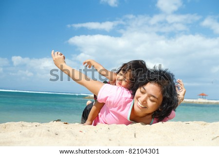 asian ethnic mother and child happy playing on tropical beach - stock photo