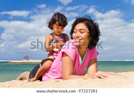Asian ethnic mother and child happy playing together at the tropical beach
