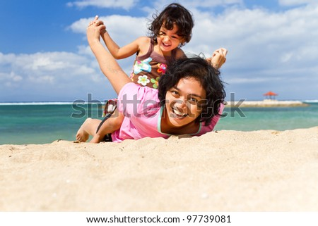 Asian ethnic mother and child happy playing together at tropical beach