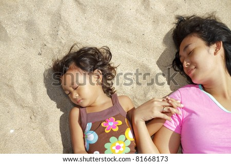 Asian ethnic mother and child lie down on the beach sand holding hands - stock photo
