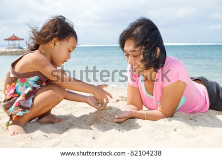 asian ethnic mother and child playing with white sand on tropical beach - stock photo