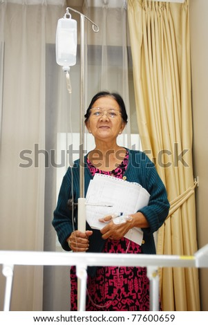 asian ethnic sick senior patient portrait in hospital ward holding lab result - stock photo