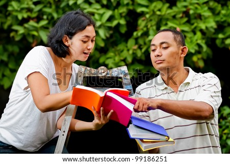 asian ethnic young adult man and woman sitting on a ladder discuss their study - stock photo