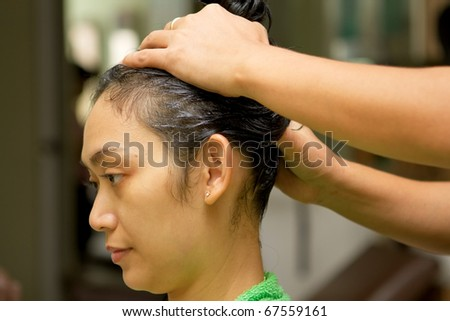 Asian ethnic young woman having hair massage at salon - stock photo