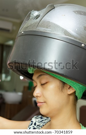 Asian ethnic young woman having hair steaming at salon - stock photo