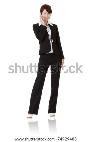Asian executive woman talking on cellphone and smiling, full length portrait isolated on white background. - stock photo