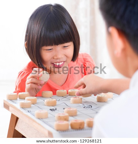 Asian family at home. Asian children playing Chinese chess at home. - stock photo
