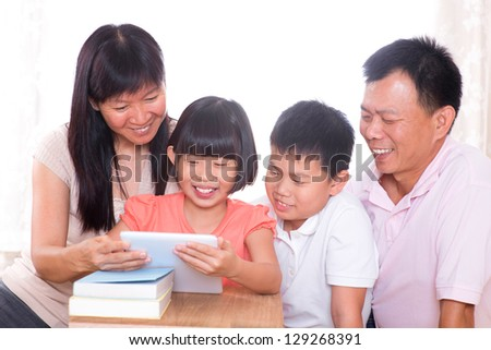 Asian family at home. Parents and children using digital tablet computer together. - stock photo