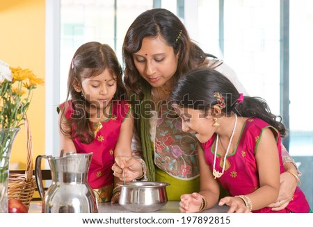 Asian family cooking food together at home. Indian mother and children preparing meal in kitchen. Traditional India people with sari clothing.
