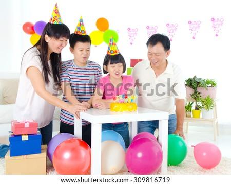 Asian family enjoying birthday party at home - stock photo