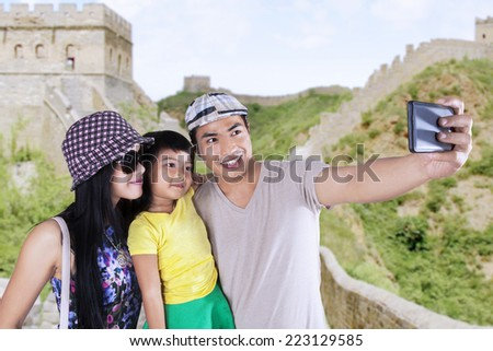 Asian family enjoying holiday and take self portrait together on Great Wall of China - stock photo