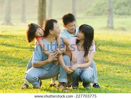 asian family enjoying outdoor at the park - stock photo