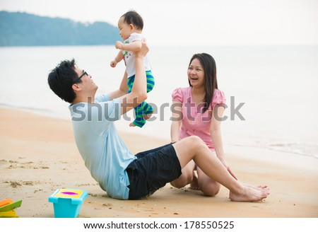 asian family enjoying quality time on the beach with father, mother and daughter - stock photo