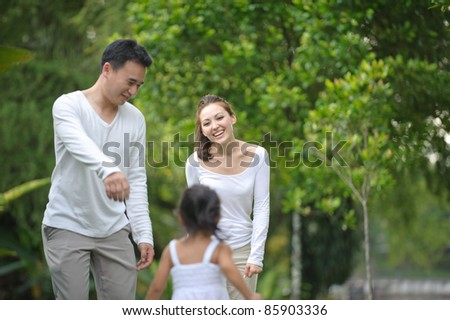 Asian family enjoying time in the park - stock photo