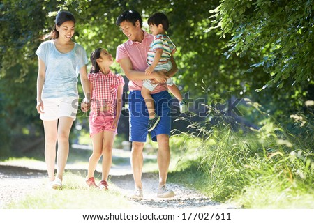 Asian Family Enjoying Walk In Countryside - stock photo