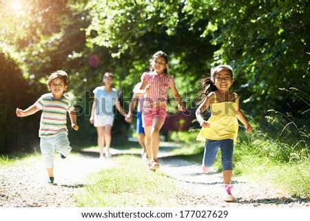 Asian Family Enjoying Walk In Countryside - stock photo