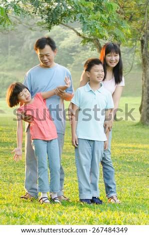 Asian Family Enjoying Walk In Summer Countryside - stock photo