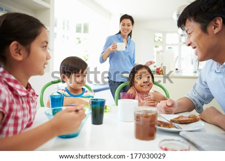 Asian Family Having Breakfast Together In Kitchen