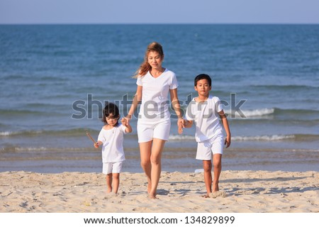 Asian family hold hands and walk on tropical beach - stock photo