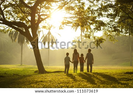 Asian family holding hands and walking towards light - stock photo