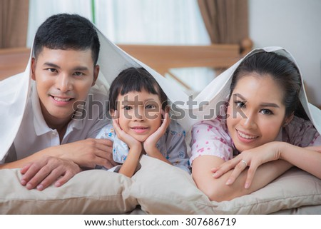 Asian Family in the duvet smiling on the bed - stock photo