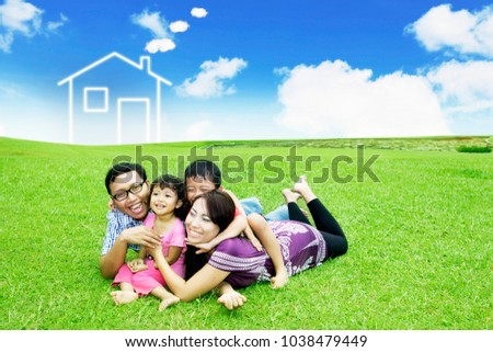 Asian family laughing together while lying in the meadow with house symbol background