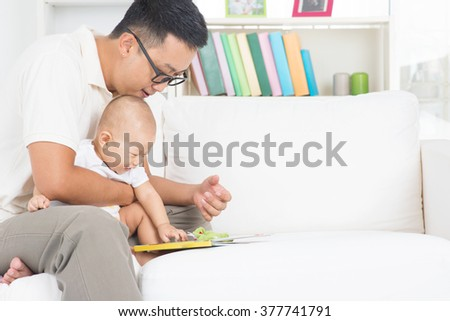 Asian family lifestyle at home. Father and child reading story book on sofa. - stock photo