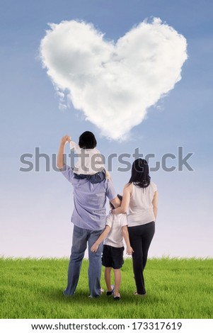 Asian family looking at clouds in the shape of a heart on a green field. - stock photo