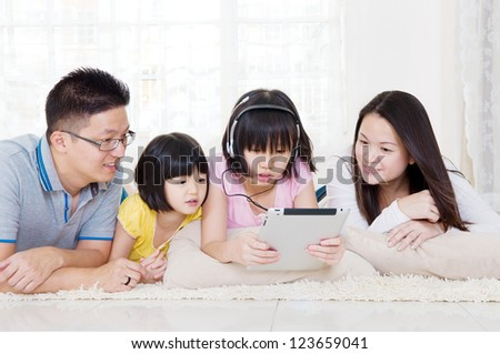 Asian family lying on floor using tablet computer - stock photo