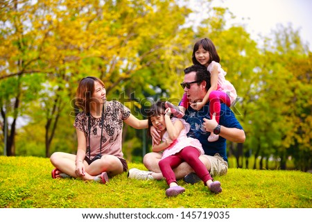 Asian family lying outdoors being playful and smiling, Outddor portrait - stock photo