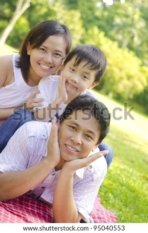 Asian family lying outdoors smiling - stock photo