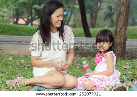 Asian family, mother and her baby was smiling in the park, vintage tone - stock photo