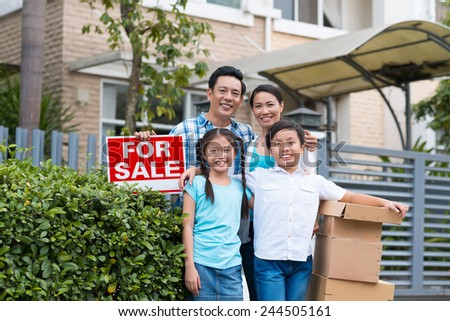 Asian family of four standing near for sale sign in front of the house
