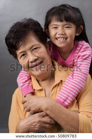asian family of granddaughter hugging her grandmother - stock photo