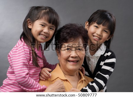 asian family of two granddaughters hugging their grandmother - stock photo