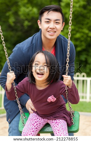 Asian family on a swing in park - stock photo