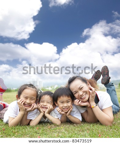 asian family on the grass with cloud background - stock photo