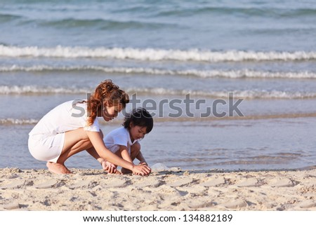 Asian family  on tropical beach - stock photo