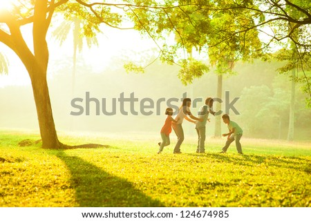 Asian family outdoor quality time enjoyment, asian people playing during beautiful sunrise - stock photo