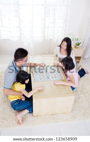 Asian family playing chinese chess - stock photo