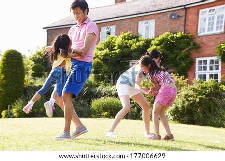 Asian Family Playing In Summer Garden Together - stock photo
